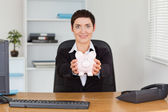 Smiling office worker holding a piggybank — Stock Photo