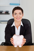 Portrait of a smilling office worker holding a piggybank — Stock Photo