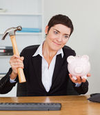 Smiling office worker breaking a piggybank with a hammer — Stock Photo