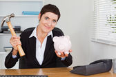 Cute office worker breaking a piggybank with a hammer — Stock Photo
