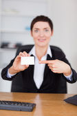 Portrait of a secrertary pointing at a blank business card — Stock Photo
