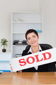 Portrait of a real estate agent with a sold panel — Stock Photo