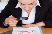 Close up of a woman looking at a chart with a magnifying glass — Stock Photo