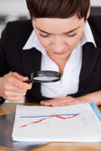 Businesswoman looking at a chart with a magnifying glass — Stock Photo