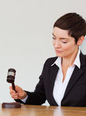 Portrait of a woman knocking a gavel — Stock Photo