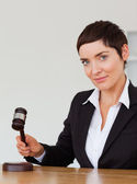 Portrait of a serious woman knocking a gavel — Stock Photo