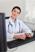 自分のコンピューターに入力する魅力的な女性医師の肖像画 — ストック写真