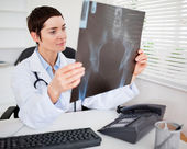 Young female doctor looking at X-ray — Stock Photo