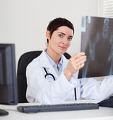 Focused female doctor holding a set of X-ray — Stock Photo