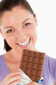 Portrait of a good looking woman eating a chocolate block while — Foto de Stock