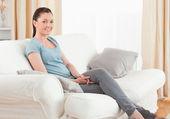 Mujer hermosa posando mientras estaba sentado en un sofá — Foto de Stock