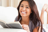 Close up of a charming woman lying on sofa reading a book lookin — Stock Photo
