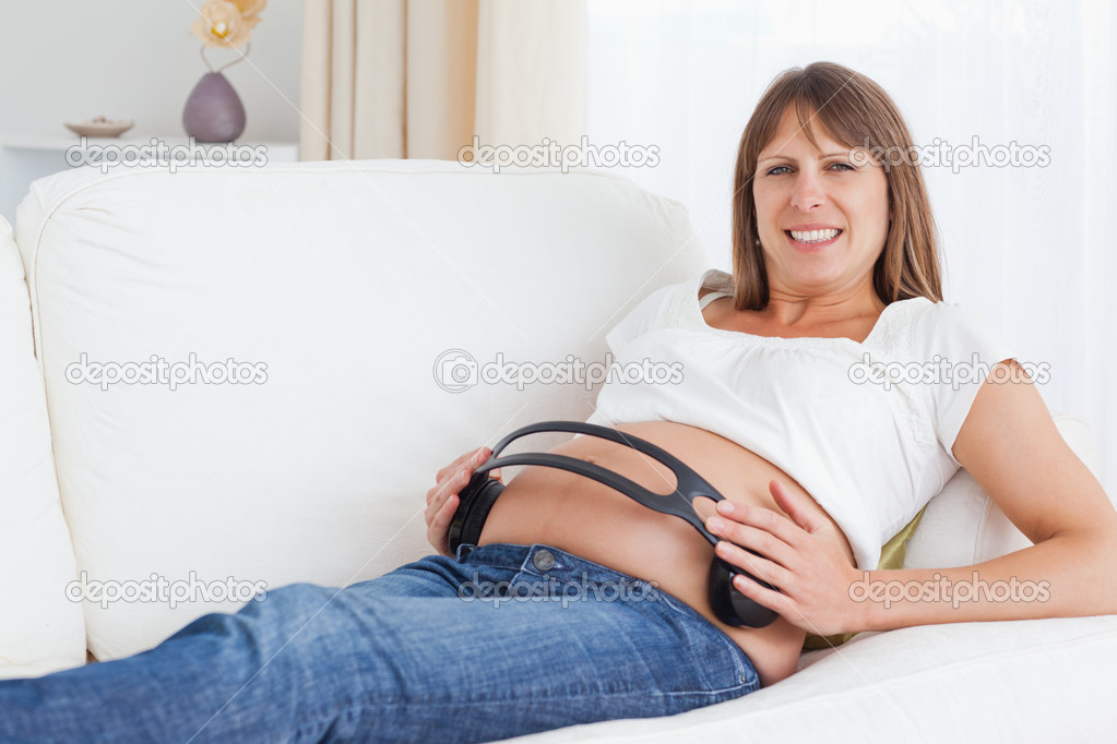 Smiling pregnant woman with headphones on her belly looking at the camera — Foto Stock #11177184
