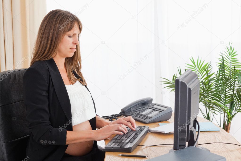 Charming pregnant woman working with a computer at the office — Stock Photo #11177191