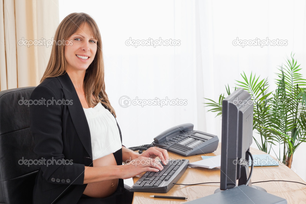 Lovely pregnant woman working with a computer at the office — Stock Photo #11177193