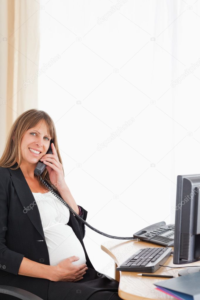 Good looking pregnant woman on the phone while working at the office — Stock Photo #11177206