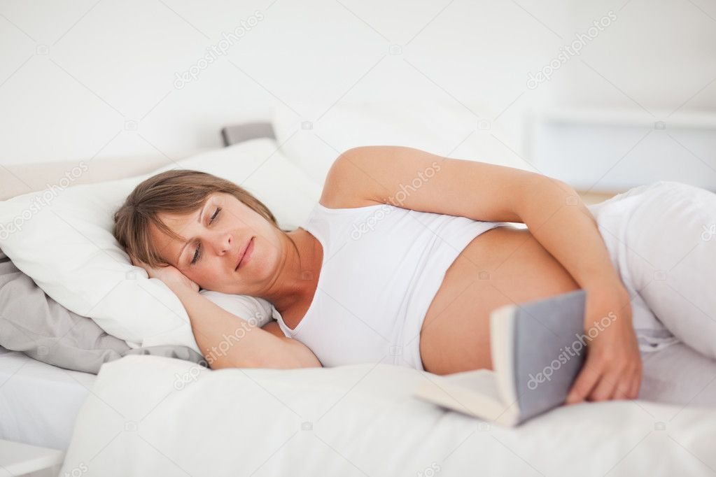 Beautiful pregnant woman reading a book while lying on her bed in her apartment — Stock Photo #11177328