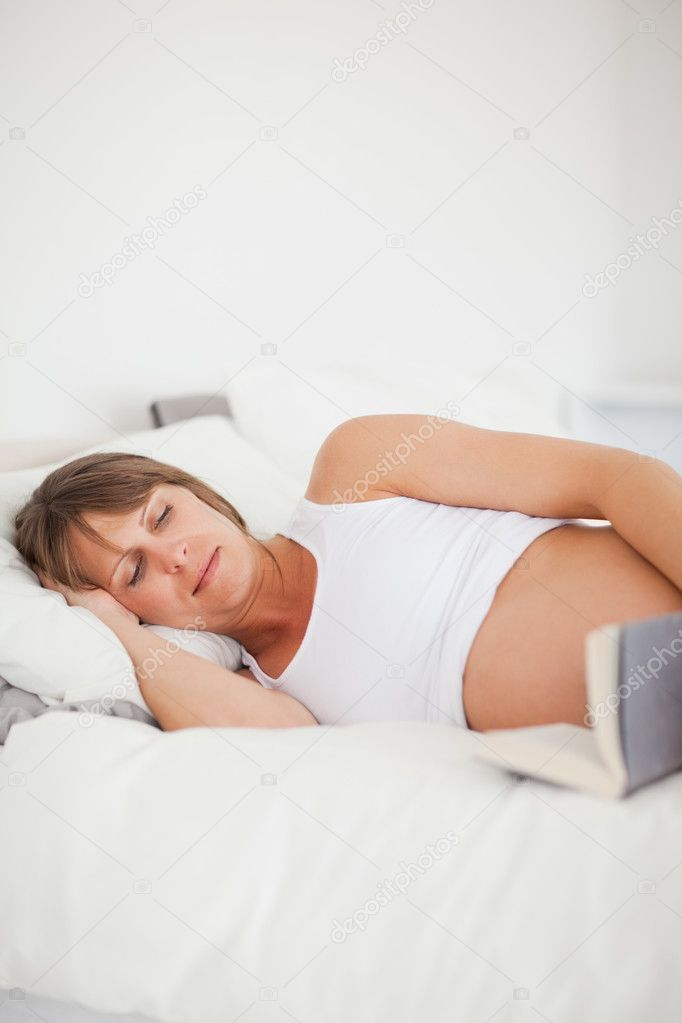 Good looking pregnant woman reading a book while lying on her bed in her apartment — Stock Photo #11177330