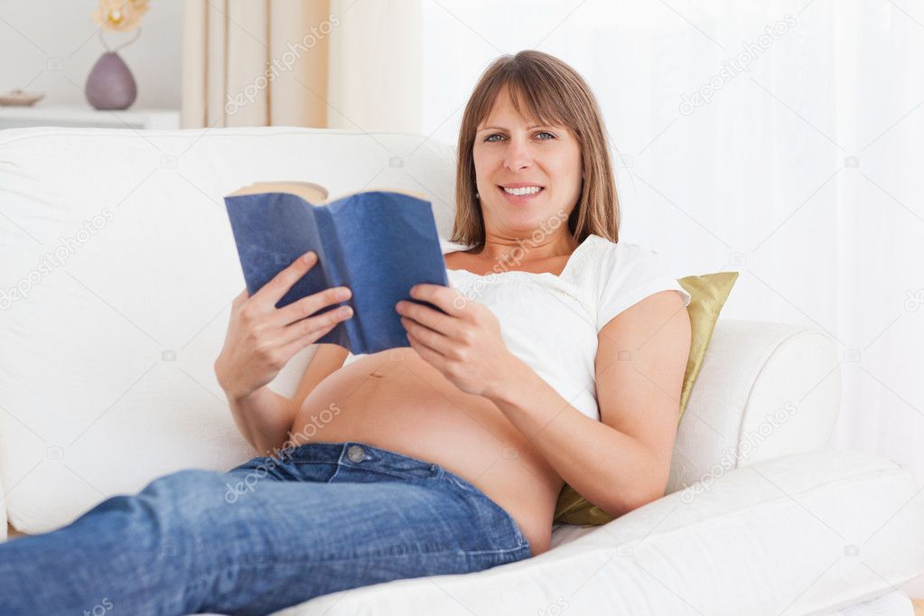 Happy pregnant woman reading a book while looking at the camera — Stock Photo #11177726