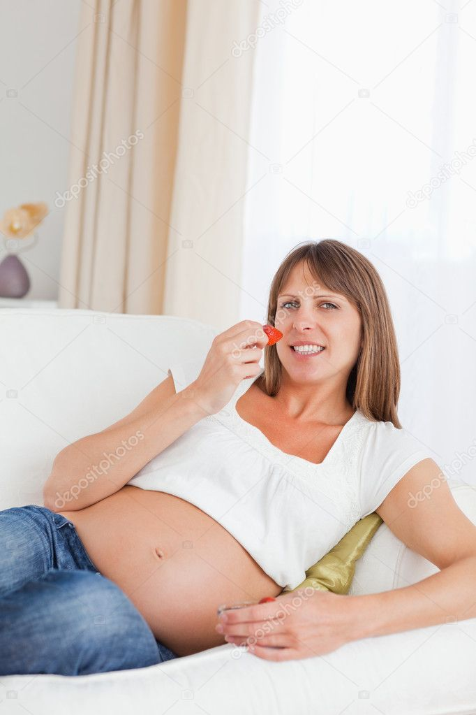 Beautiful pregnant woman eating strawberries while lying on her sofa — Stock Photo #11177747