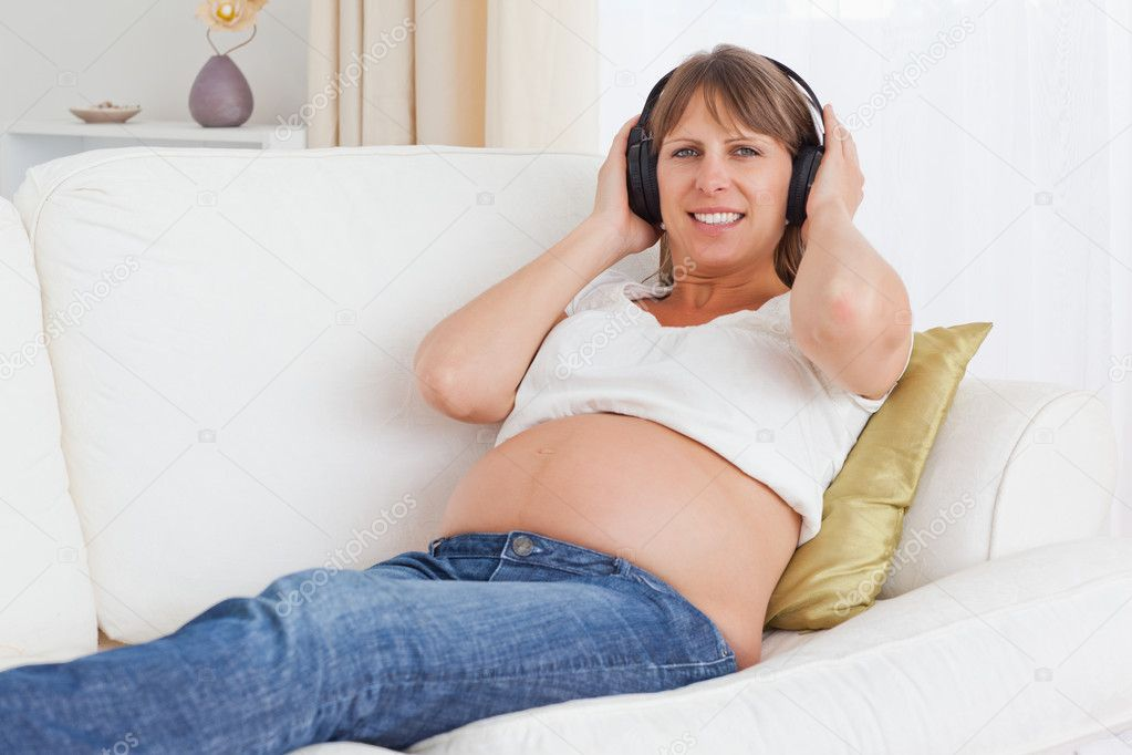 Pregnant woman listening to music while lying on a sofa — Stock Photo #11177750