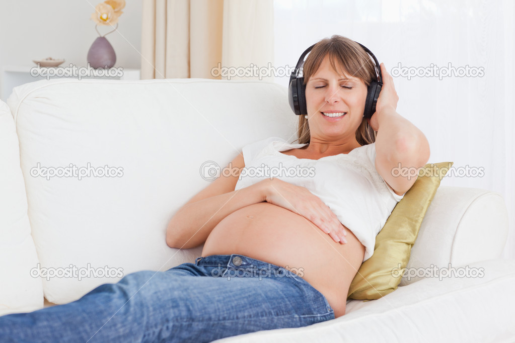Happy pregnant woman listening to music in her lving room — Stock Photo #11177788
