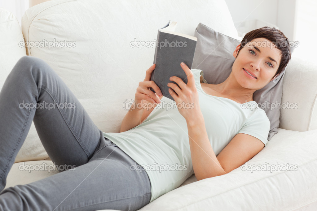 Beautiful brunette holding a book while looking at the camera  Stock Photo #11178116