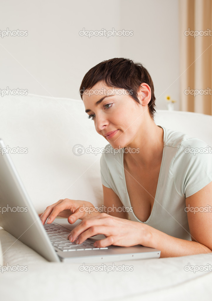 Portrait of a gorgeous short-haired woman using a laptop in her living room  Stock Photo #11178411