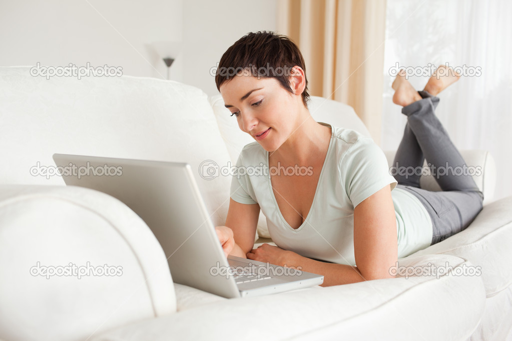 Smiling short-haired woman using a laptop in her living room — Stock Photo #11178414