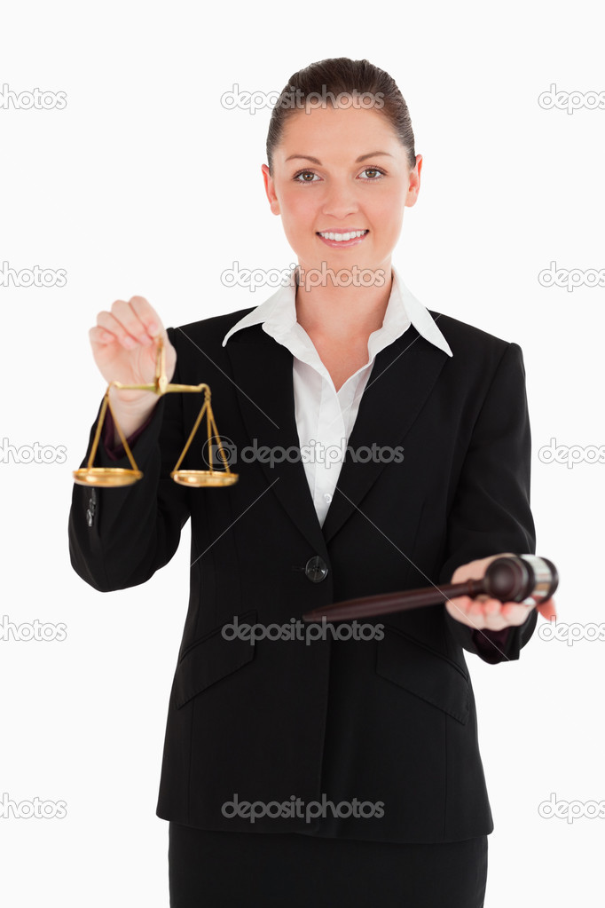 Good looking woman in suit holding scales of justice and a gavel while standing against a white background — Stock Photo #11179319