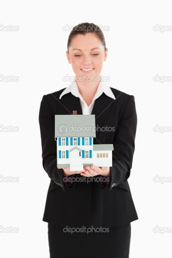 Attractive woman in suit holding a miniature house while standing against a white background — Stock Photo #11179412