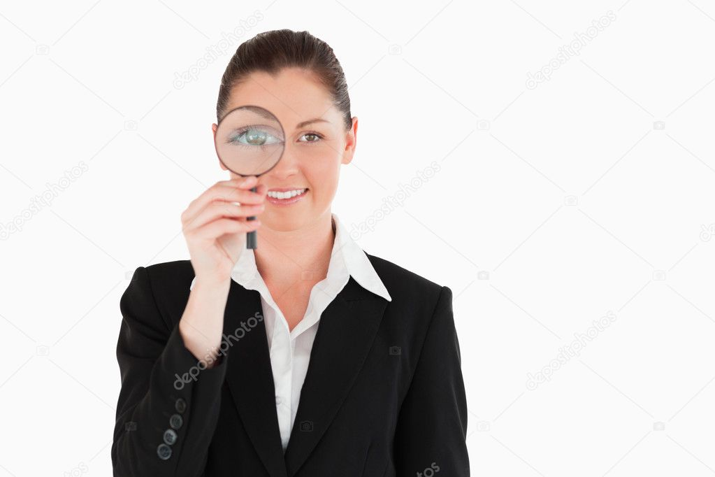 Charming woman in suit holding a magnifying glass while standing against a white background — Stock Photo #11179425