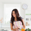 Attractive woman consulting a notebook while cooking vegetables — Stock Photo #11180492