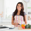 Good looking woman consulting a notebook while cooking vegetable — Stock Photo #11180493