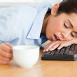 Pretty woman sleeping on a keyboard while holding a cup of coffe — Stock Photo