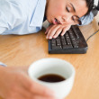 Gorgeous woman sleeping on a keyboard while holding a cup of cof — Stock Photo #11180670