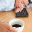 Cute woman sleeping on a keyboard while holding a cup of coffee — Stock Photo #11180671