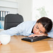 Frontal view of a pretty woman sleeping on a keyboard while hold — Stock Photo #11180672
