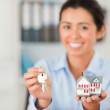 Good looking woman holding keys and a miniature house while look — Stock Photo #11180724