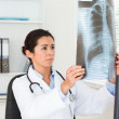 Stock Photo: Gorgeous female doctor looking at a x-ray