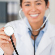 Lovely female doctor using a stethoscope while looking at the ca — Stock Photo #11180811