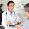 Royalty-Free Stock Photo: Patient giving his attractive woman doctor a piece of paper