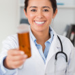 Portrait of an attractive smiling doctor holding a box of pill — Stock Photo