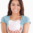 Lovely woman posing with a piggy bank — Stock Photo