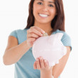 Lovely woman inserting a coin in a piggy bank - Stock Photo