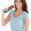 Lovely woman eating a chocolate bar — Stock Photo