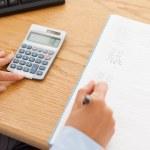 Feminine hands using a calculator and a pen — Stock Photo