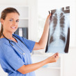 Gorgeous doctor with stethoscope and x-ray looking into camera — Stock Photo