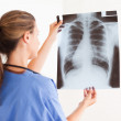 Gorgeous brunette doctor with stethoscope looking at a x-ray — Stock Photo