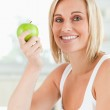 Young smiling woman holding a green apple looks into the camera — Stock Photo